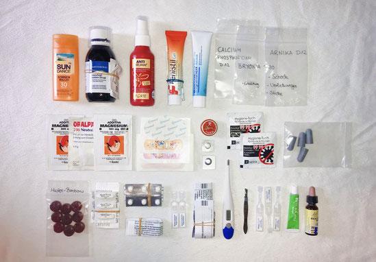 Medikamente für die Reiseapotheke aufgereiht auf einem weißen Hintergrund. Damit ist man im Urlaub ausgrüstet. Ob Verletzung, Erkältung oder Allergie, die richtigen Medikamente sind dabei!