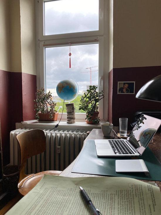 Schreibtisch mit Unterlagen, Stift, Laptop
