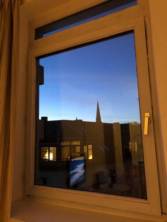 Blick aus dem Fenster auf Dächer, Abends