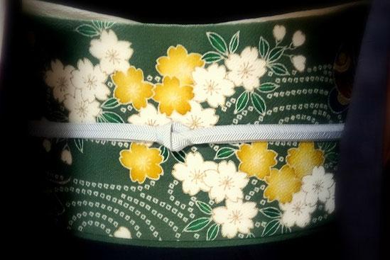 焦げ茶の紬のきものに、濃い緑の記事に桜の花を染めた久呂田明功さんの染め名古屋帯です。