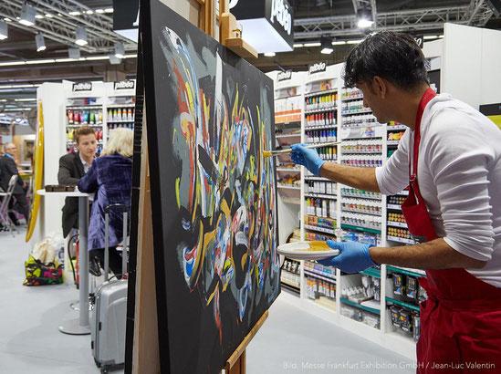 Künstler beim Malen eines Bildes mit bunten Farben auf der Creativeworld Messe in Frankurt in der Westfalen Halle