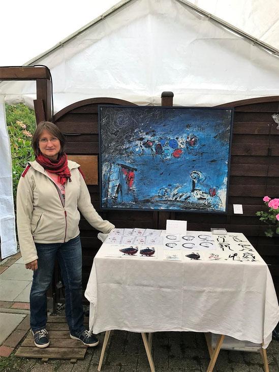 Ingrid Freihold mit einer Arbeit und handcolorierten Postkarten