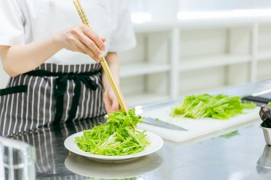 カフェのテーブルに座ってノートパソコンを広げてパート社員にレクチャーするカフェの店長。メモをとるパート社員。