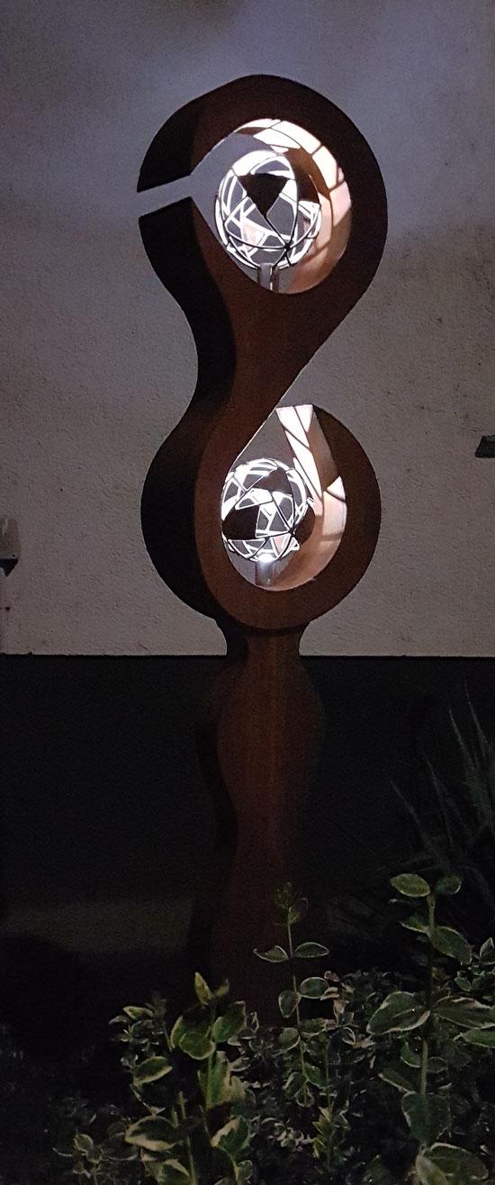 Skulptur aus Stahl mit Gitterkugeln und LED Beleuchtung.