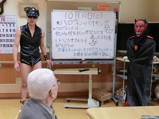「ハロウィンとは~。」ご利用者さんに必死に思いを伝える介護スタッフ。仮装した姿が、なぜか初々しい