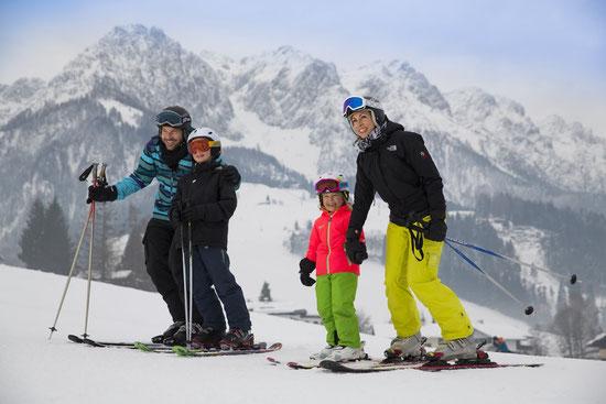 Familie mit zwei Kindern beim Skifahren