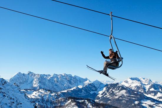Skifahrerin, die auf Sessellift sitzt und winkt