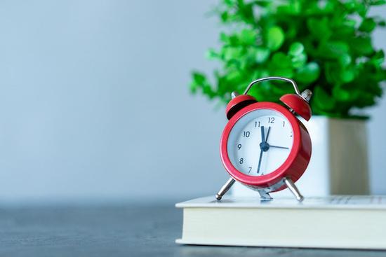 木製のデスクに置かれたバインダーファイルとボールペン。リングノートの上に置かれた白の腕時計。