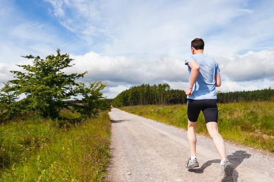 Ein Mann in Sportkleidung joggt im Freien auf einem Gehweg zwischen grüner Wiese und mit einem Wald im Hintergrund.