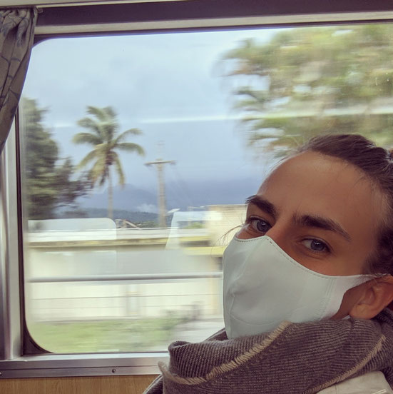 Portrait of Miss Vizzz with a Facemask in Taiwanese Train, passing through the landscape. Through the window of the train behind the artist you can se palms, houses and mountains.