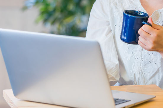 ノートパソコンを操作しながら電話するビジネスウーマン。水玉のボウタイブラウスとパールのネックレス。