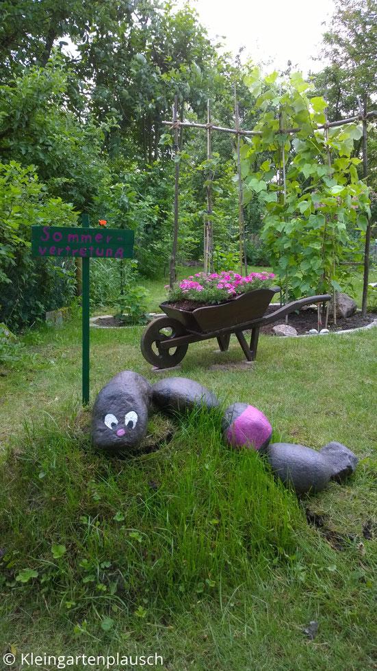"""Regenwurm mit großen Augen, aus Feldsteinen, daneben ein Schild """"Sommervertretung"""