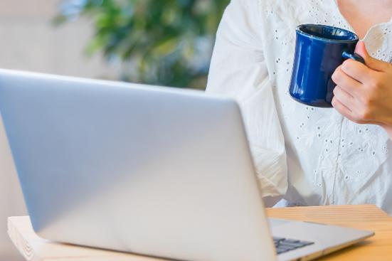 オフィスのオープンスペースでコーヒーを飲みながらノートパソコンを広げるビジネスウーマン。