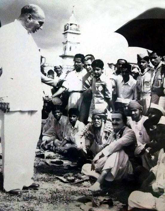1954 : Darshan programme in Ahmednagar - lunch break. Sarosh Irani ( standing ) talking to Meher Baba. Image courtesy of Lord Meher.