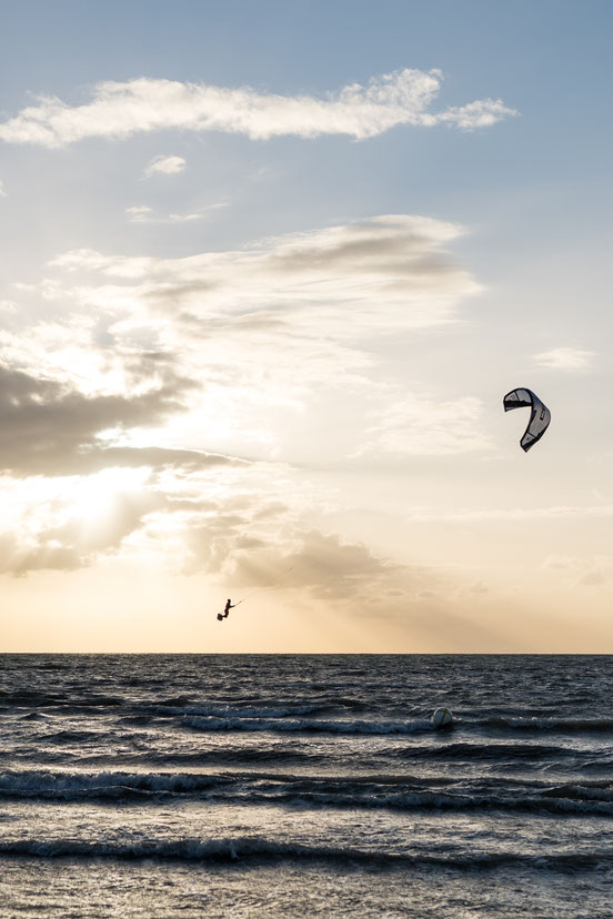 Kite surfer jumping at sunset