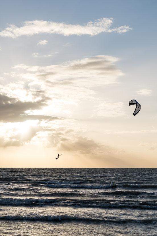 Kite surfer jumping at sunset