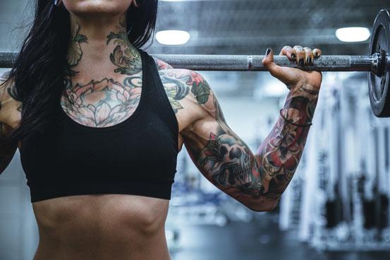 Der Oberkörper einer Frau im Fitnessstudio. Auf den Schultern hält sie eine Langhantelstange und trainiert. Sie trägt ein schwarzes und bauchfreies Top. Ihr Oberkörper ist tätowiert.