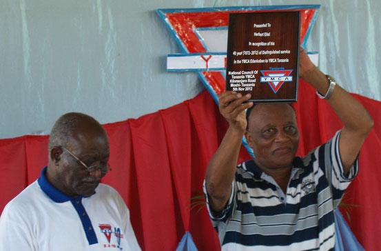 Stewart Lyatuu (Generalsekretär YMCA TZ,li. und Wlliam Kessy, Vorstand YMCA TZ (re) ehren Herbert Eitel