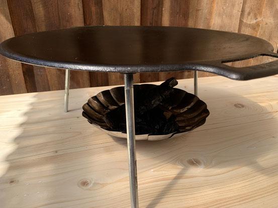 Die Muurikka 48 Grillpfanne mit Beinen über einer kleinen Feuerschale auf dem Tisch