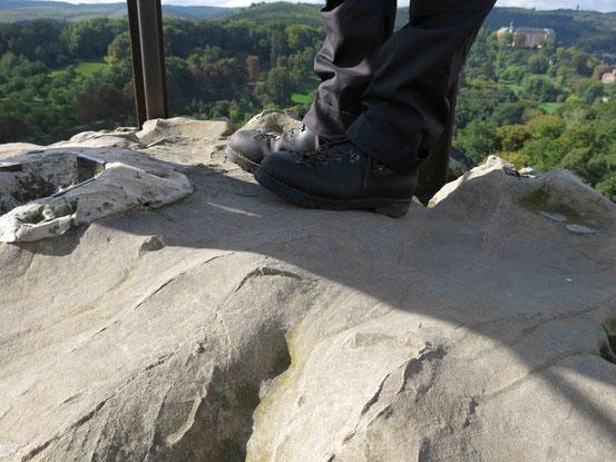 Wanderschuhe auf Felsboden, Großvaterfelsen, im Hintergrund Schloss Blankenburg
