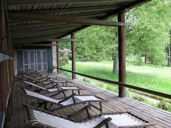 Liegehalle im Sanatorium Dr. Barner. Offenes Holzgebäude mit Liegen.