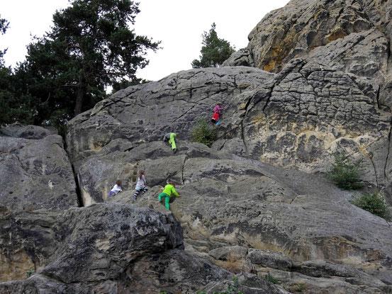 Kinder klettern auf den Felsen des Hamburger Wappens