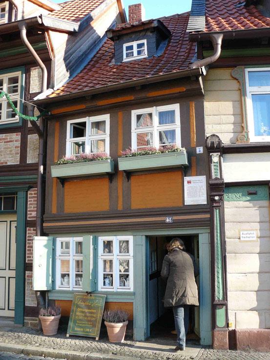 Kleinstes Haus in Wernigerode. Frau bückt sich beim Reingehen