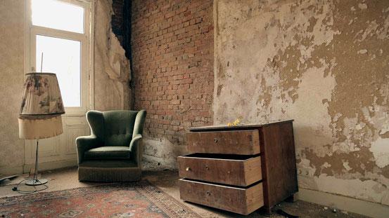 Vergessen im Harz: Ein Raum mit abgerissener Tapete, abblätterndem Putz, einem grünen Sessel, eine Kommode mit offenen Schubladen und einem alten, geblümten Lampenschirm