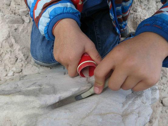Kind schabt Sand aus Sandstein und füllt es in eine rote Dose