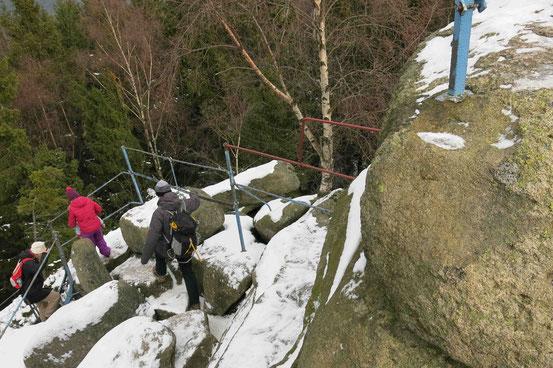 Drei Menschen gehen vom Aussichtsplatz an den Schnarcherklippen nach unten