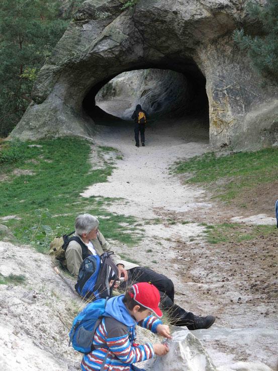 Ein Mann und ein Kind machen Pause vor einer Sandstein-Höhle am Hamburger Wappen bei Timmenrode/ Harz
