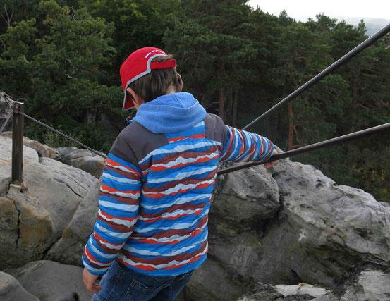 Kind steigt von Großvaterfelsen bei Blankenburg ab, hält sich am Geländer fest