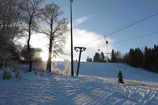 """Ski-Centrum """"Am Brande"""" in Hohegeiß. Schlepplift mit Skifahrern im Gegenlicht"""