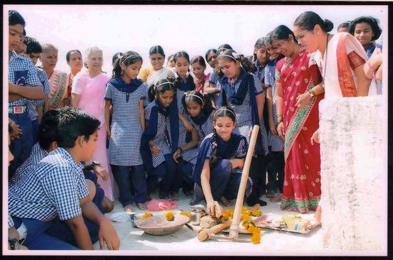 Sai Kelkar, MBUP, 7th grade student and Dr. Mrs. Kelkar's granddaughter (breaking coconut offering)