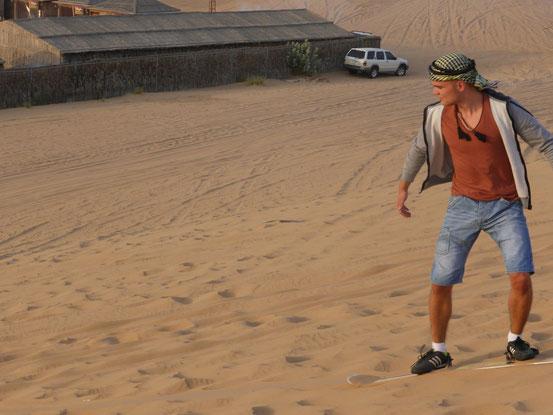 Ich fahre mit dem Board eine Sanddüne hinab.