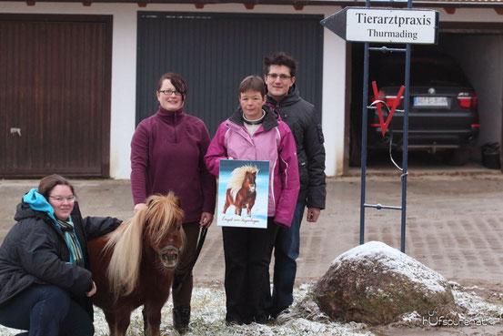 """Künstlerin Hanna Stemke neben Pony """"Engel"""", Besitzerin Nana Keck mit dem Hufspuren-Gemälde und Klinikchef Dr. Menzel (v.l.n.r.)"""
