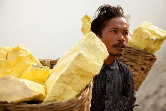 Bis zu 100 Kilo wiegen die mit Schwefel gefüllten Bambuskörbe, die einheimische Arbeiter auf ihren Schultern aus dem Krater des Gunung Ijen tragen.