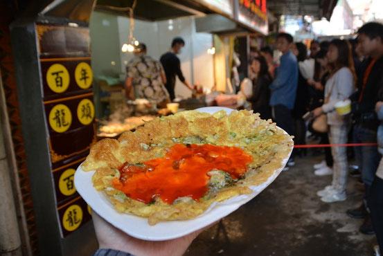 30分ほど列んでゲットした「海蛎煎(HaiLiJian)」は牡蠣が散りばめられているチヂミのような食べ物。15元。