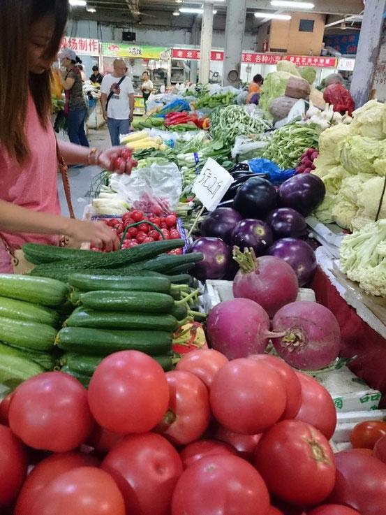 ココの市場はみんなキレイに陳列されててそれなりに美味しく見えます。愛ちゃんが選んでるプチトマトは「5元2斤≒100円/kg」です。