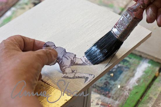 Auf dem Foto wird die Technik für das Aufbringen des Decoupage Lackes von Annie Sloan erklärt