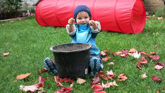 Ein Kind spielt mit Herbstblätter