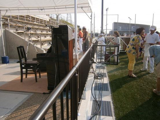 会場の人達と談笑するピアノ伴奏の加藤先生