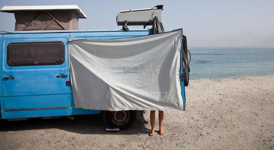 Erfrischende Büssli-Dusche am Strand von Musandam.