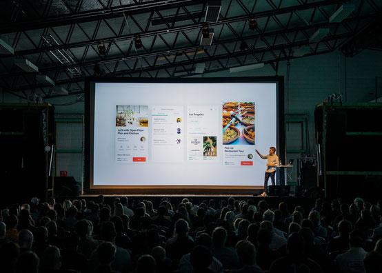 Symbolbild Übersetzerkonferenz: ein Redner steht auf der Bühne und zeigt seine Präsentation auf einem großen Bildschirm