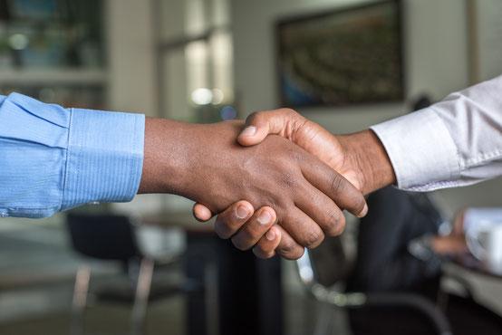 Symbolbild für einen Übersetzungsauftrag: zwei Personen schütteln sich die Hände zum Vertragsabschluss