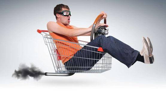 mann in einkaufswagen, der losdüst