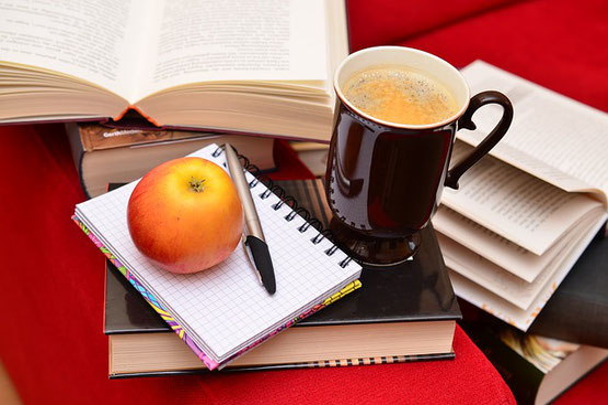 赤いソファのうえに乱雑に積まれた書籍。コーヒーの入ったマグカップ、メモ、ペン、りんご。