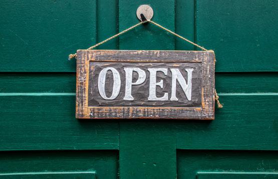 """Grüne Holztür, daran hängt ein Schild mit der Aufschrift """"Open"""""""