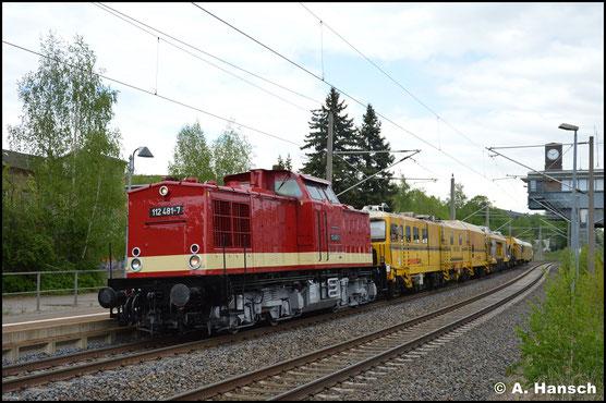 Mit ganz neuem Gesicht donnert die Lok mit einem Bauzug am 3. Mai 2020 durch Chemnitz-Hilbersdorf Hp. Als 112 481-7 ist sie für MaS Bahnconsult Leipzig im Einsatz