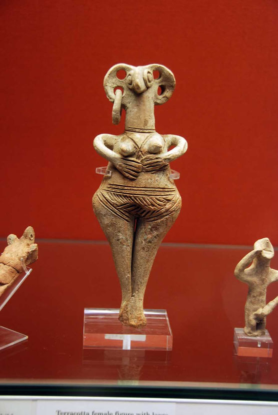 Terracotta figure with pierced ears and hands under her breasts, 1450-1200BC: British Museum